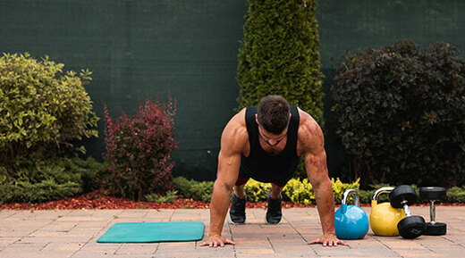 Man doing push-ups next to weights in the back yard