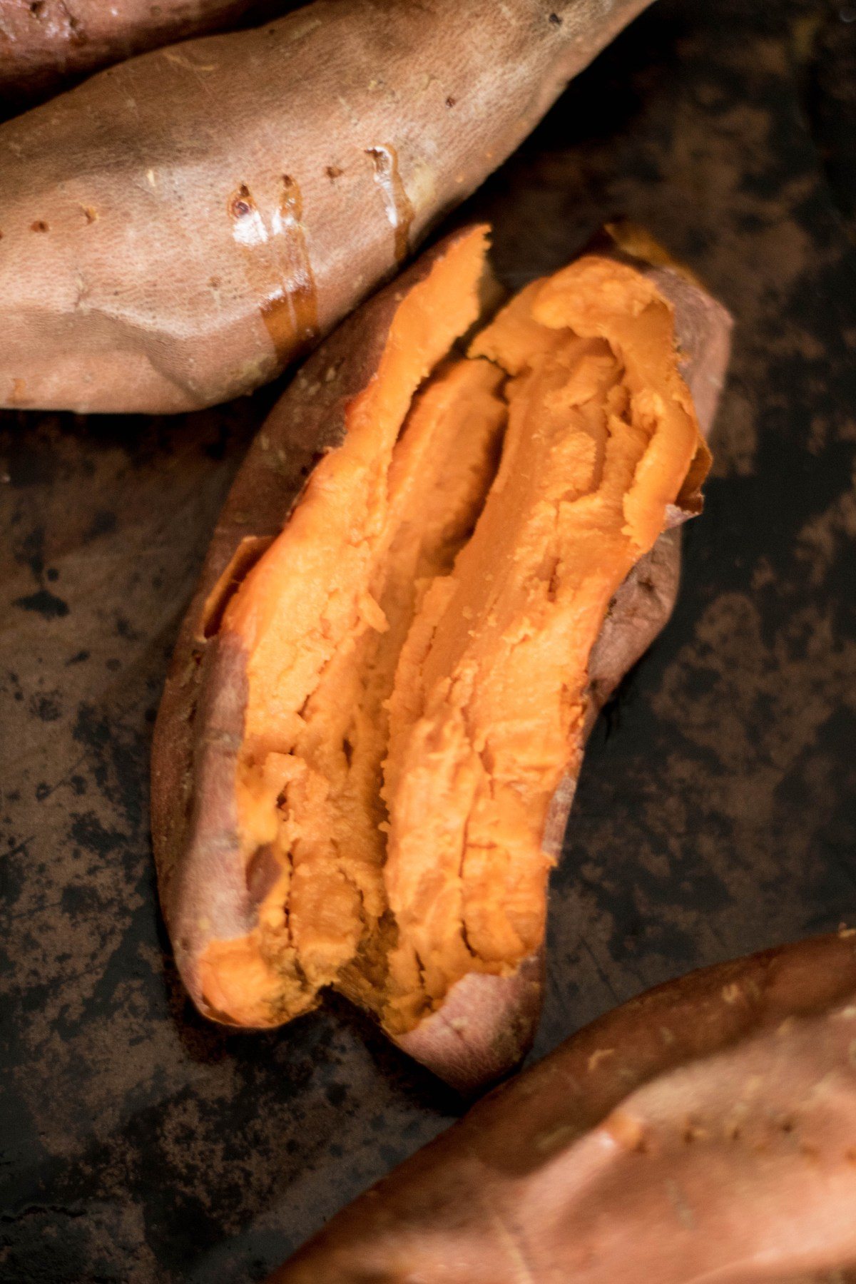 Oven baked sweet potato laying on black background