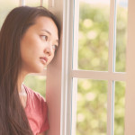 A sad woman looking out a window longing for something more in her life.