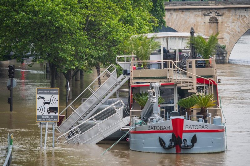 epa05340820 A view of the Seine river from Saint Louis Island, shows a partially submerged restaurant boat, in Paris, France, 01 June 2016. Heavy rains hit a quarter of the French territory over several days causing floods. EPA/CHRISTOPHE PETIT TESSON