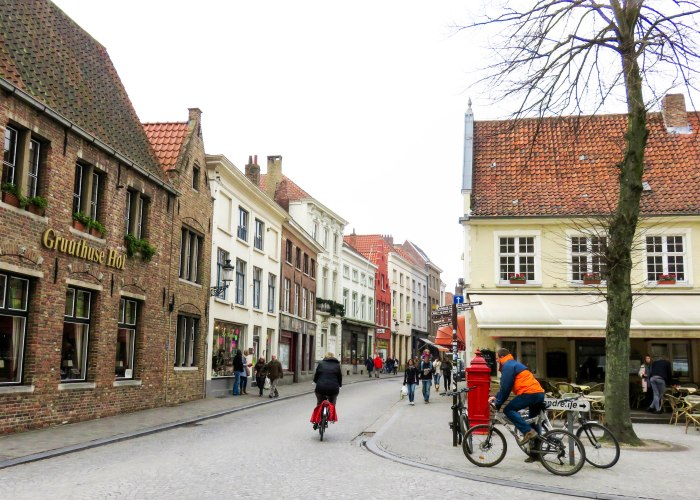 a square in bruges with restaurants and cyclists
