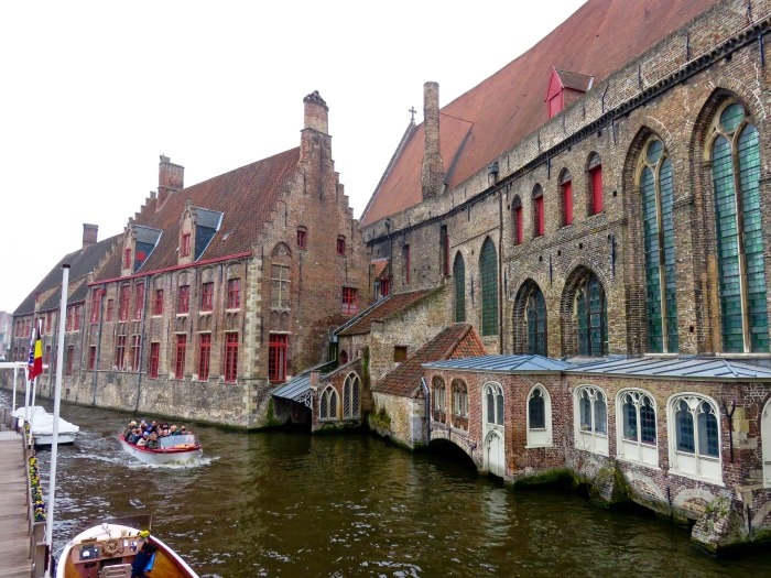 view of buildings on a canal in bruges with tourist boats