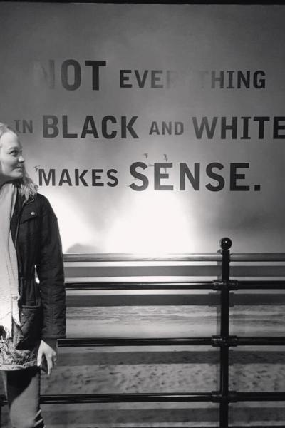 a black and white image of alex at the guinness factory tour looking at an ad that reads not everything in black and white makes sense