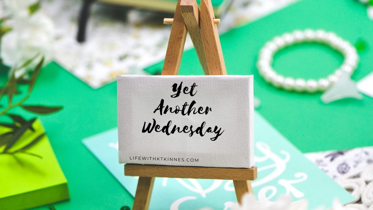 small easel with yet another wednesday written on it in black brush strokes against a green, gold and aqua background.
