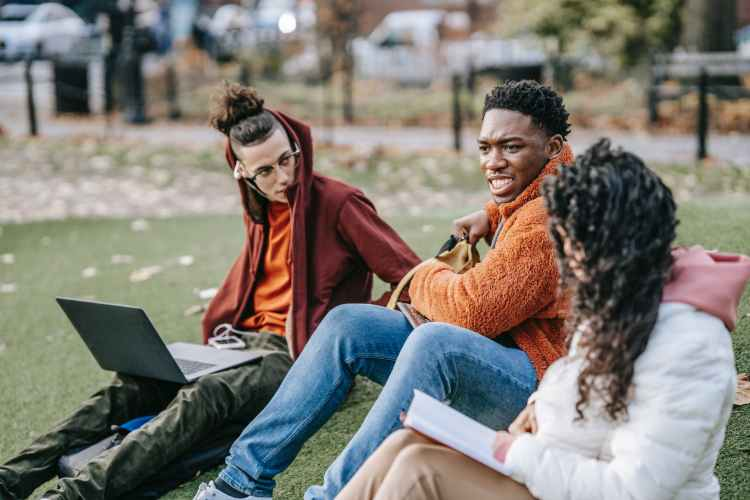 multiethnic students sitting in park