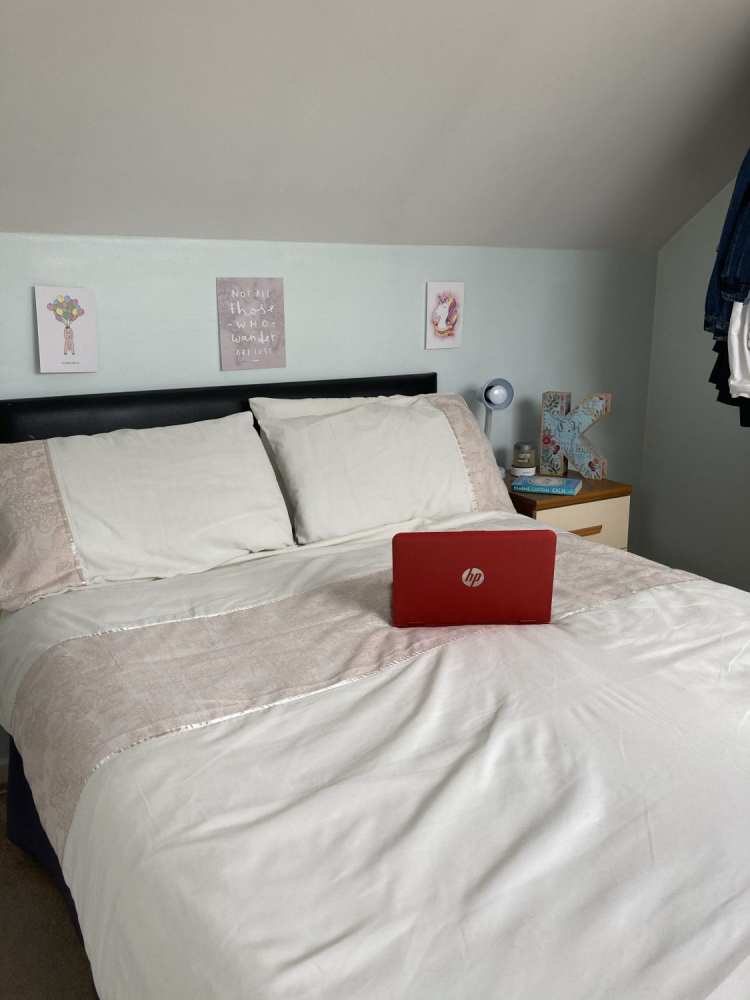 White bedding with laptop in centre of double bed - creating a home holiday feel