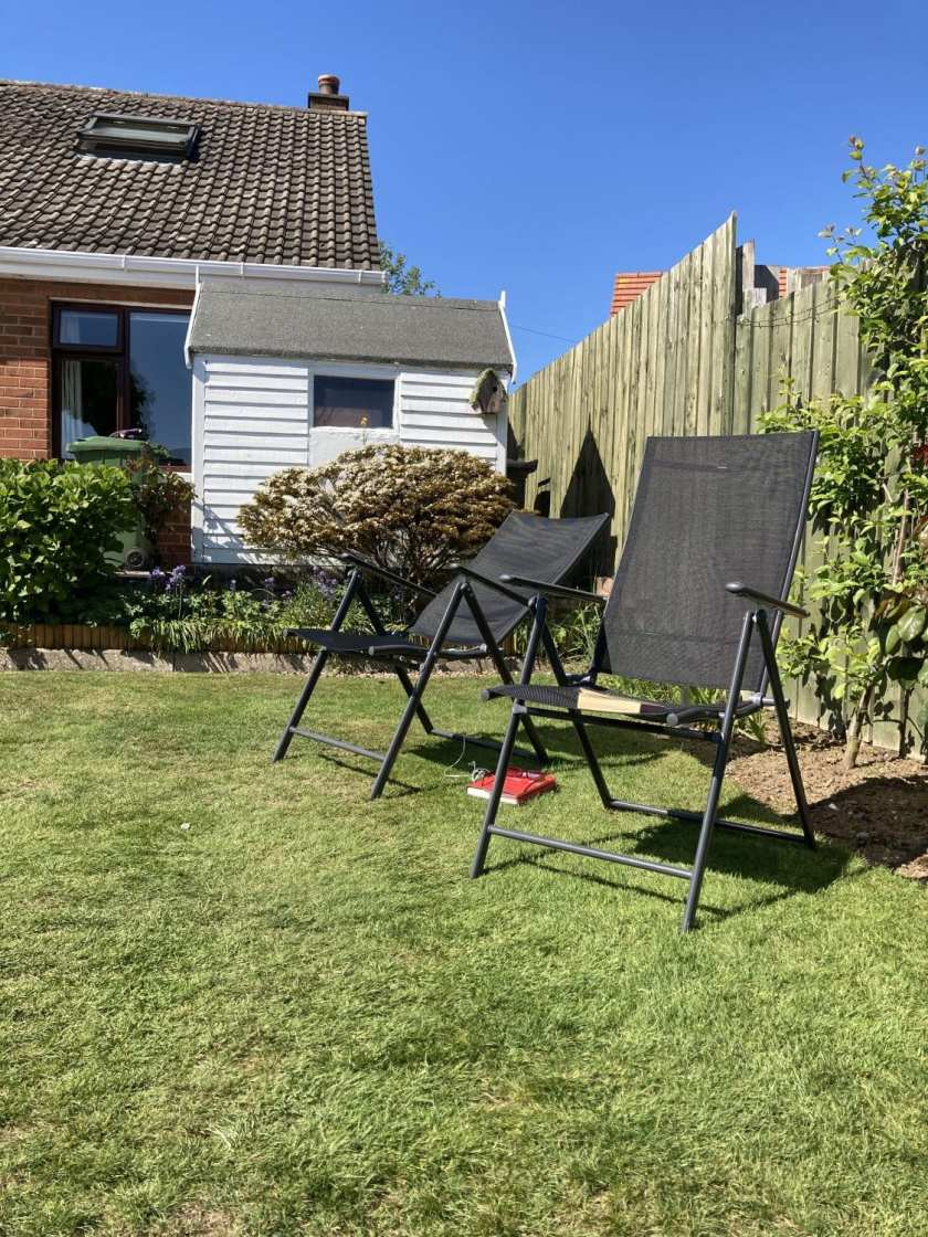 Sun loungers in a back garden set up for a home holiday