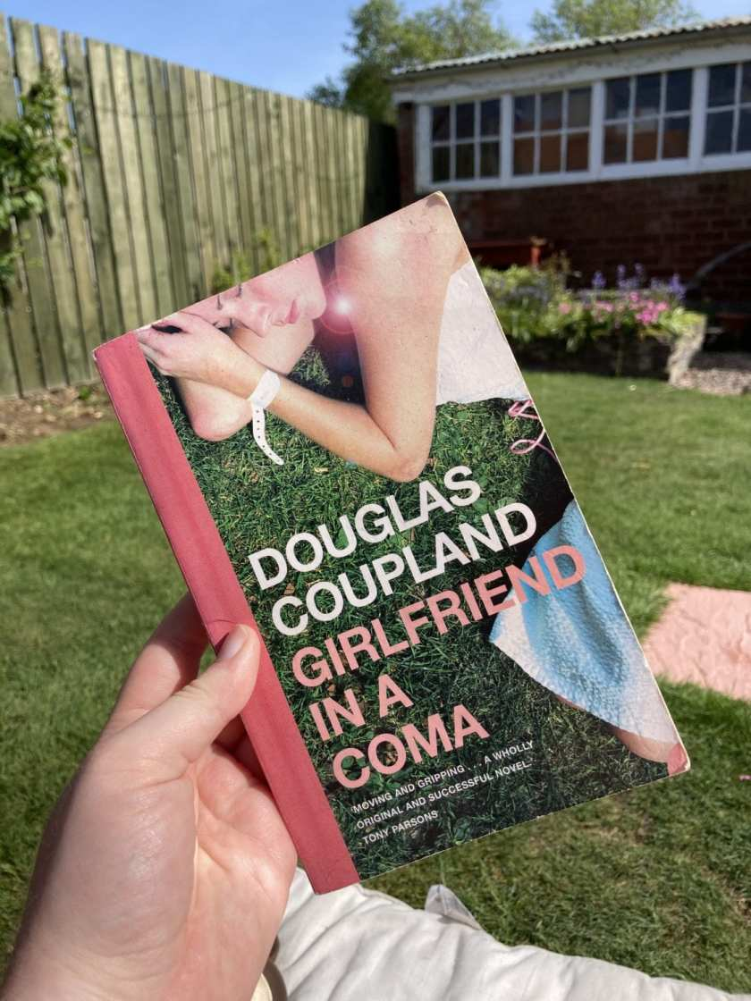 Girlfriend In A Coma Book Cover in forefront, with a back garden in the background