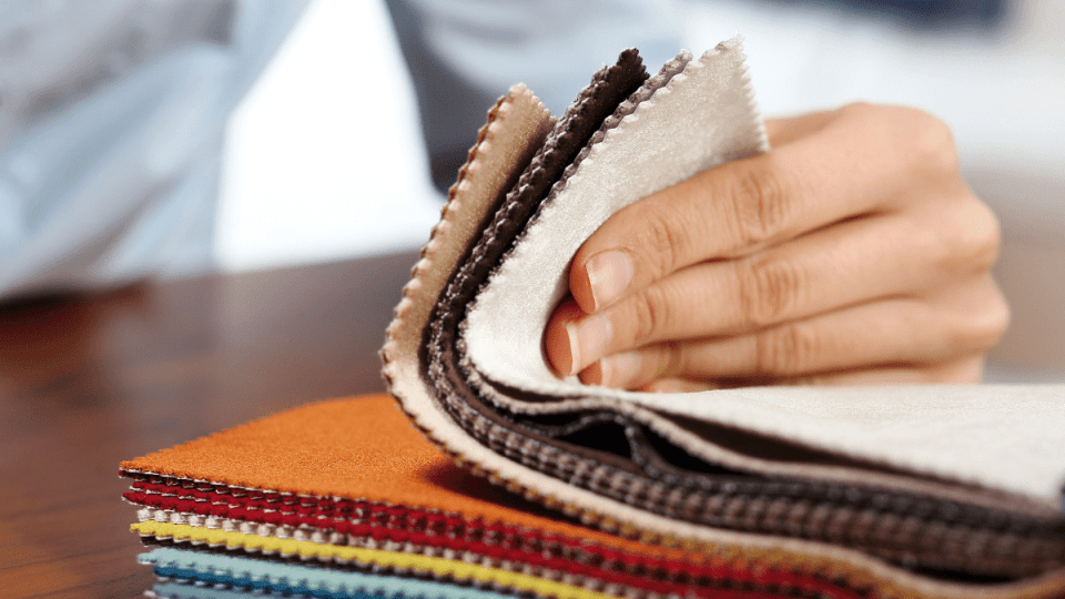 Unseen person flicking through fabric swatches for reupholstering
