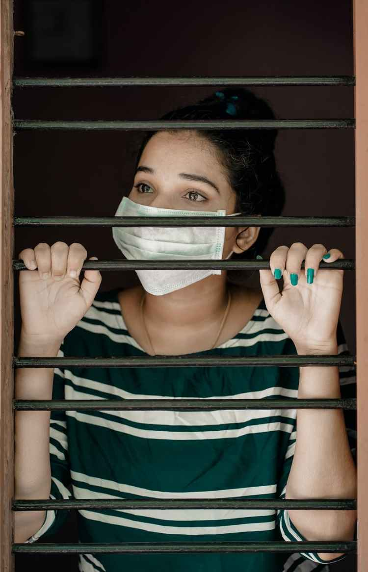 woman in green and white stripe shirt covering her face with white mask due to covid restrictions, looking out a barred window to represent lockdown.