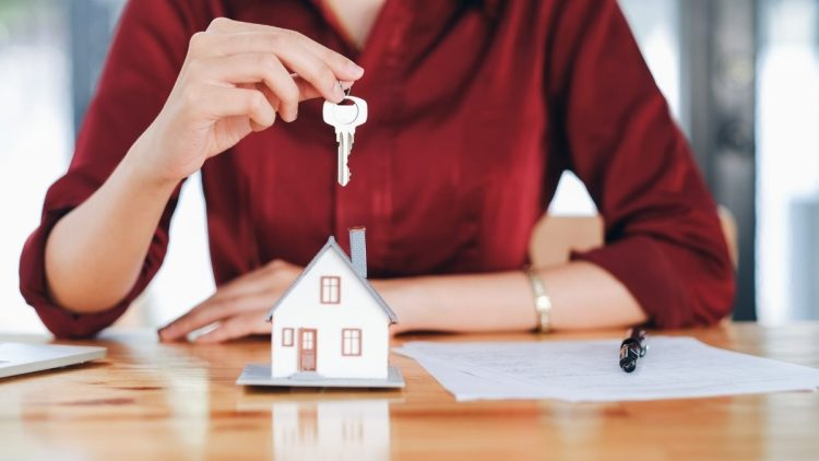 Woman in red shirt holding out a key above a house. It is unclear from the image whether the recipient is renting vs buying the property.