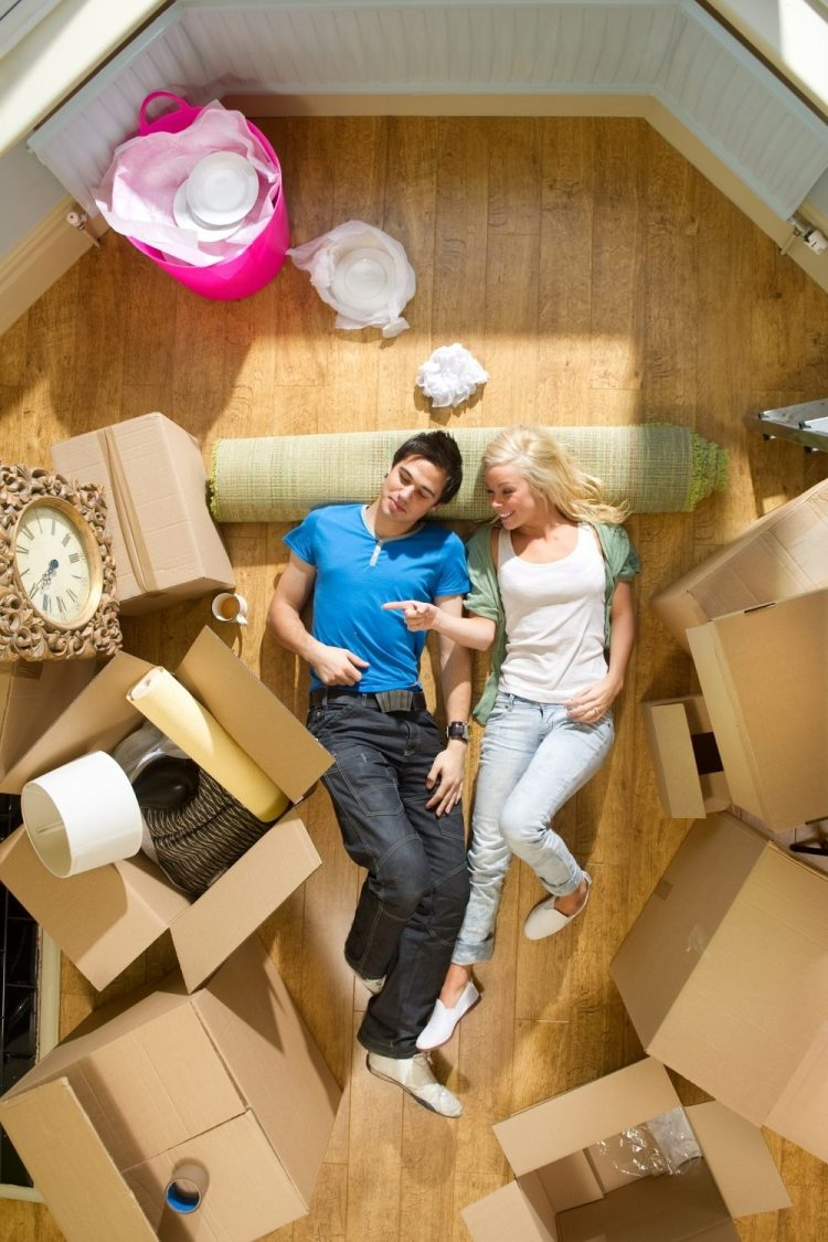 couple lying on floor of a new property surrounded by moving boxes.