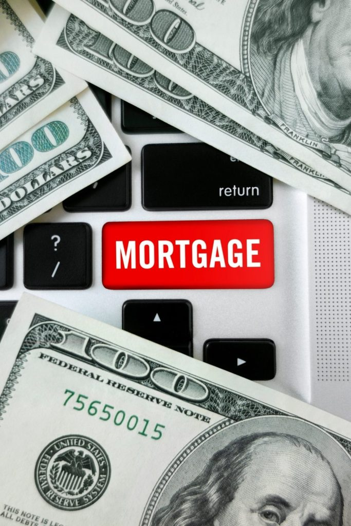 Red button on keyboard reading Mortgage, surrounded by $100 bills