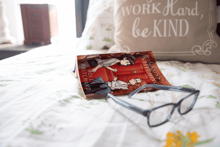 A paperback copy of Cross Stitching lying open, pages down, on a bed