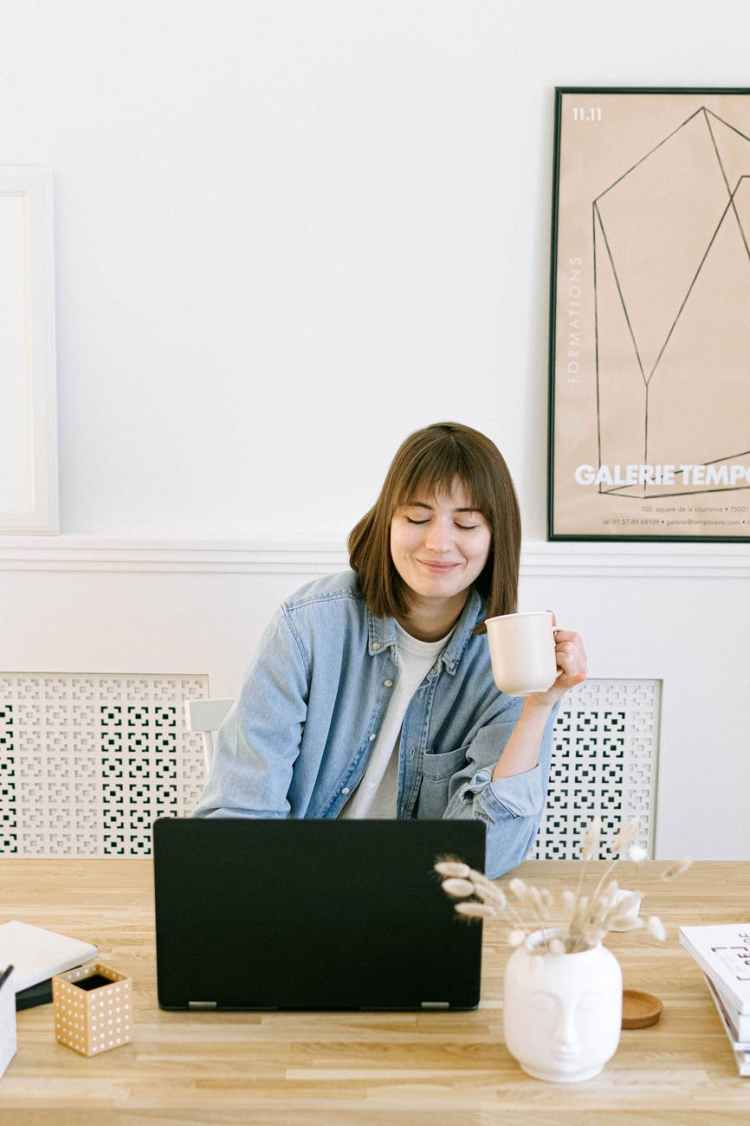 woman drinking coffee and looking at a laptop blogging in September 2021