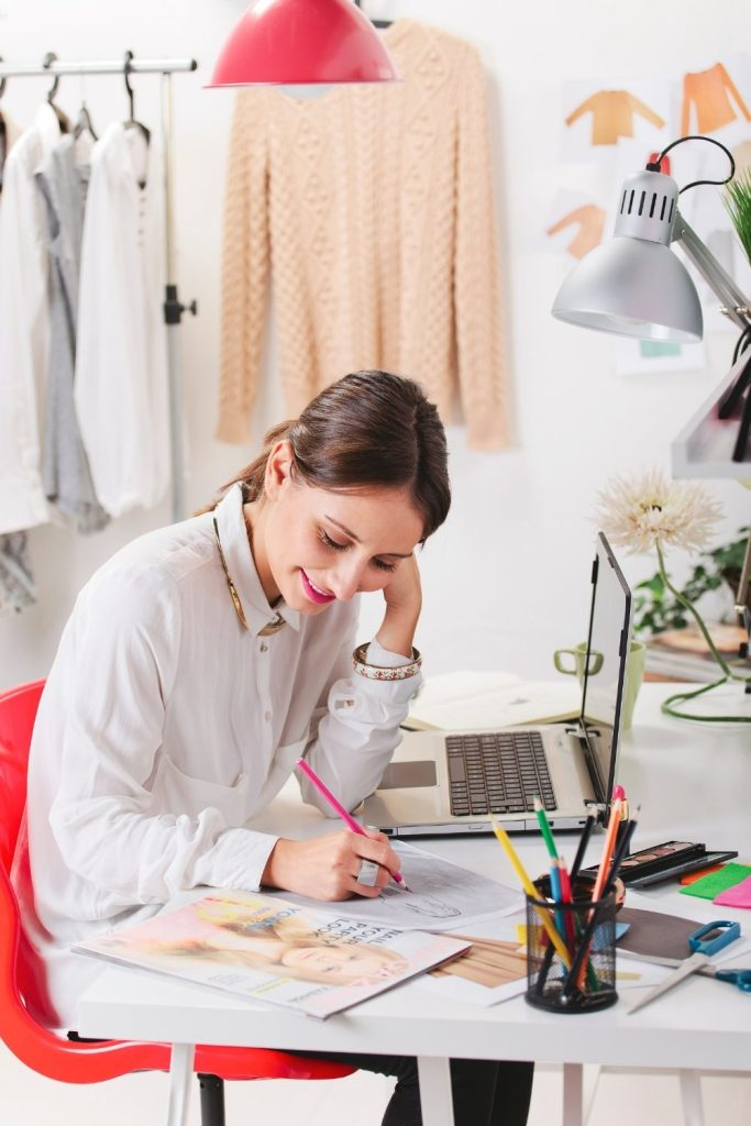 Woman smiling while sorking on her laptop and sketching