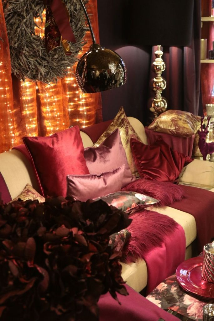 A cosy Christmas living room decorated in various shades and hues of red rugs, throws and cushions.