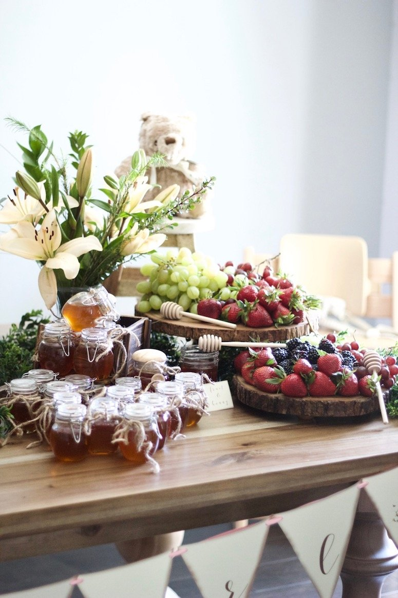 Classic Winnie the Pooh baby shower, a tablescape full of fruit and honey for the guests! Click to see more photos from this beautiful baby shower