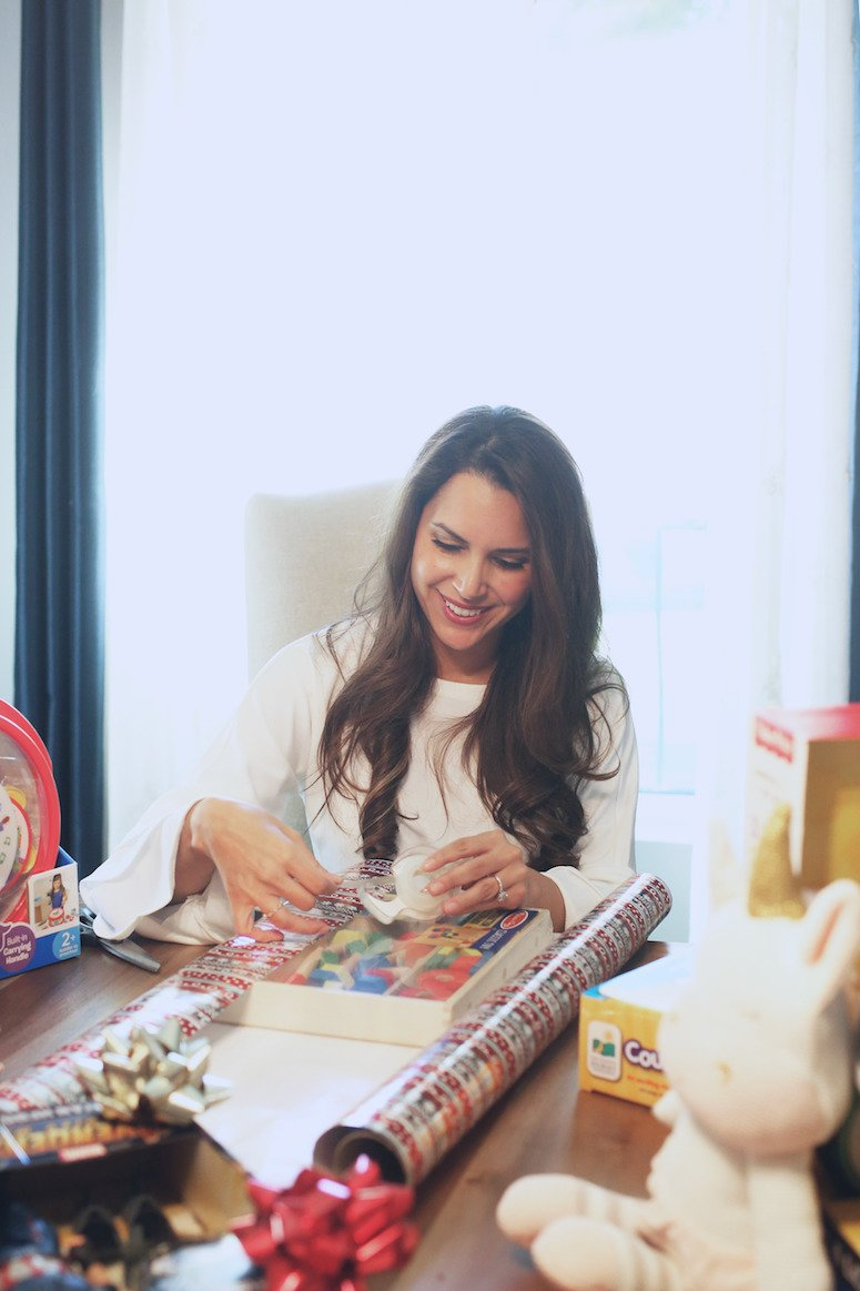 Brunette woman wrapping a Christmas gift   The ultimate toddler christmas gift life   Lifewithmar.com