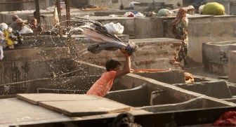 Clothing is slapped on concrete to clean it. A human agitator.