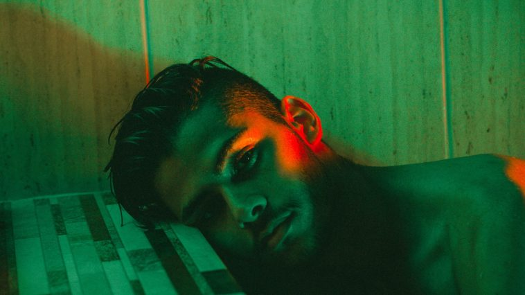 My Experience Of Dealing With Anxiety As A Man sad man lying down in green light