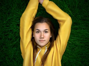 Young woman laying on the grass girl with yellow sweater and hands up lxp lifexpe