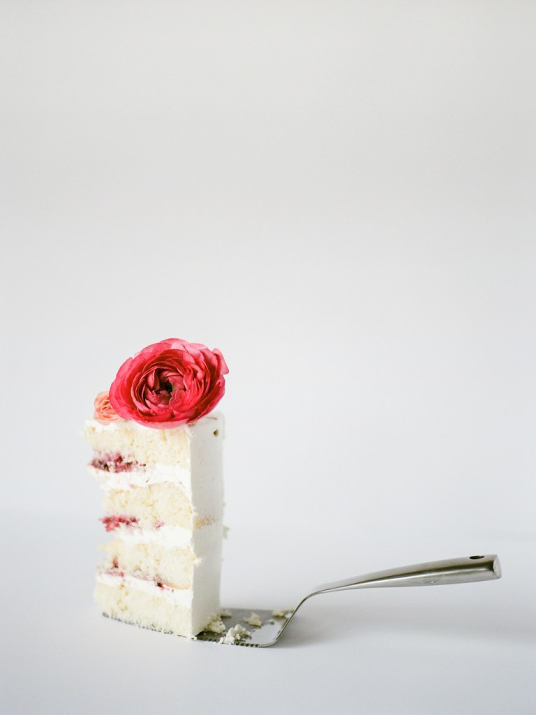 slice of cake with flower on top by Whisk Bakery