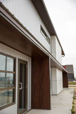 Close up of entrance to commercial multi door building with aluminum siding and Hardie panel exterior