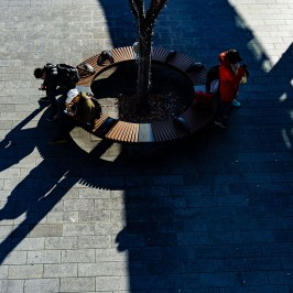 People in the sun and shadow in bench