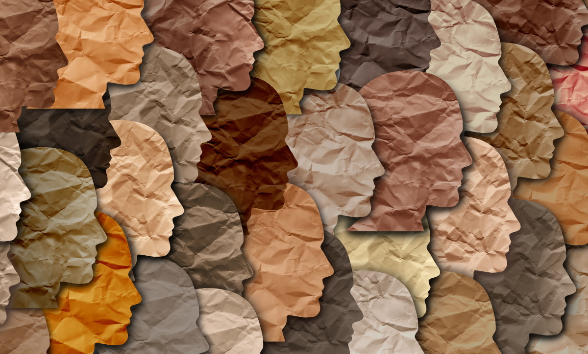 cutouts of paper faces in a variety of skin tones