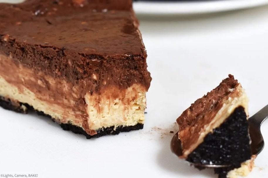 Slice of the Peanut Butter Chocolate Cheesecake. This is a three layer,baked cheesecake. An Oreo crust, a peanut butter cheesecake and chocolate cheesecake. Creamy, salty and sweet. This is the chocolate and peanut butter lovers cheesecake and tastes just like a Reese's peanut butter cup. #chocolatepeanutbuttercheesecake