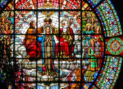 Colorful stained glass depicting the Virgin Mary being honored