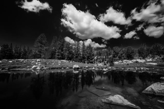 Summer clouds reflect in a rocky pond alongside the trail to Native Lake on Clay Butte in the Beartooth mountains of northwest Wyoming.