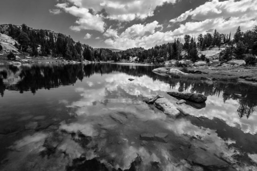 Clouds reflect in Native Lake on a summer day. The lake is located on Clay Butte, an unusual geological formation in the Beartooth mountains of northwest Wyoming.