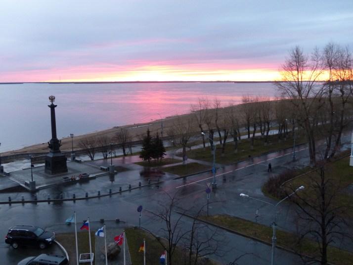 Sateinen ilta Vienanjoen rannalla. Vasemmalla patsaan nokassa Venäjän kaksipäinen kotka. Alhalla näkyy myös Suomen lippu.