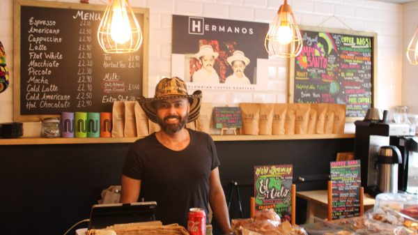 man wearing a sombrero stood in front of a counter thats filled with pastry inside a coffee shop called hermanos