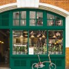 An orange bike resting on green shopfront which has cool graphics and sign that says farmstand in the window