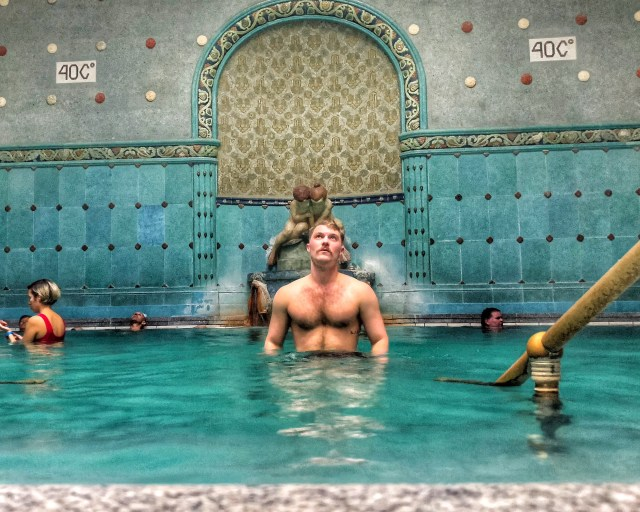 topless man standing in a pool in front of blue tiled walls at gellert baths