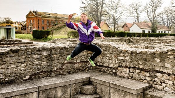 man wearing 90's style purple sports jacket holding glasses leaping of the ground in front of ancient roman ruins in budapest