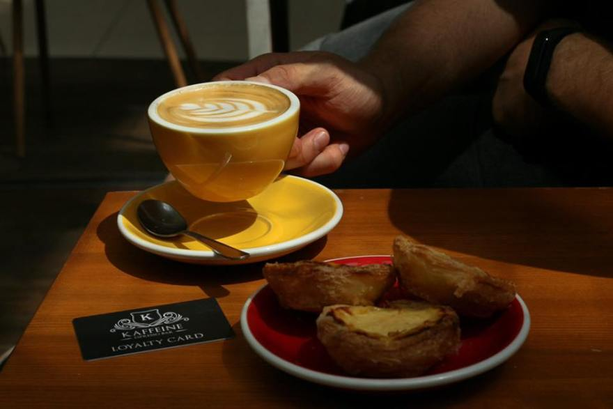 "hand holding a yellow cup with a cappucino and red plate with three pasteis de nata and a black card which says ""kaffeine budapest loyalty card"""