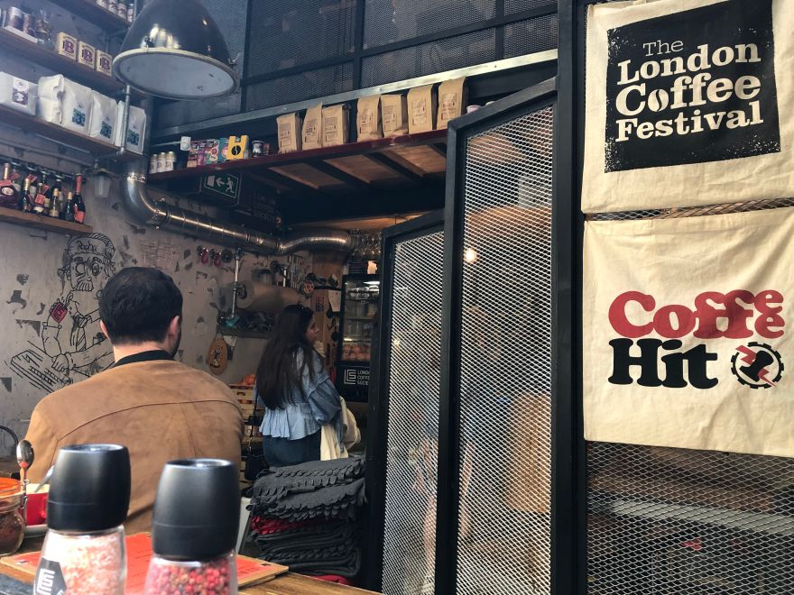 "man with a suede jacket sat inside a coffee shop in budapest which has a black decor and reusable bags that say ""the london coffee festival"" and ""coffee hit"""
