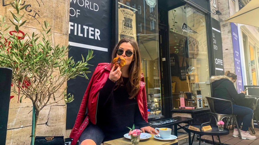 girl with red leather jacket and black sunglasses eating a croissant outside a coffee shop in budapest