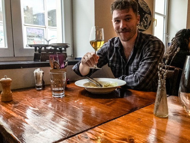man with moustache drinking wine and eating pasta in
