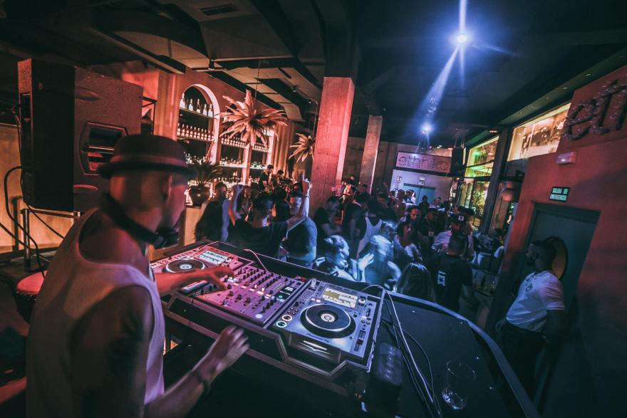 dj-on-decks-mixing-music-in-neon-lit-space-with-people-dancing