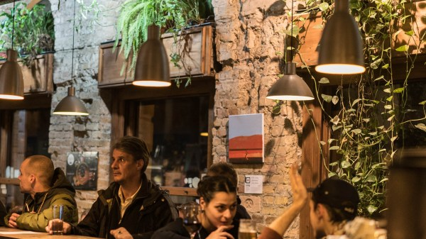 people drinking at bar with plants in budapest's 7th district