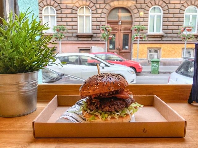seed bun burger in front of window in budapest's 7th district restaurant