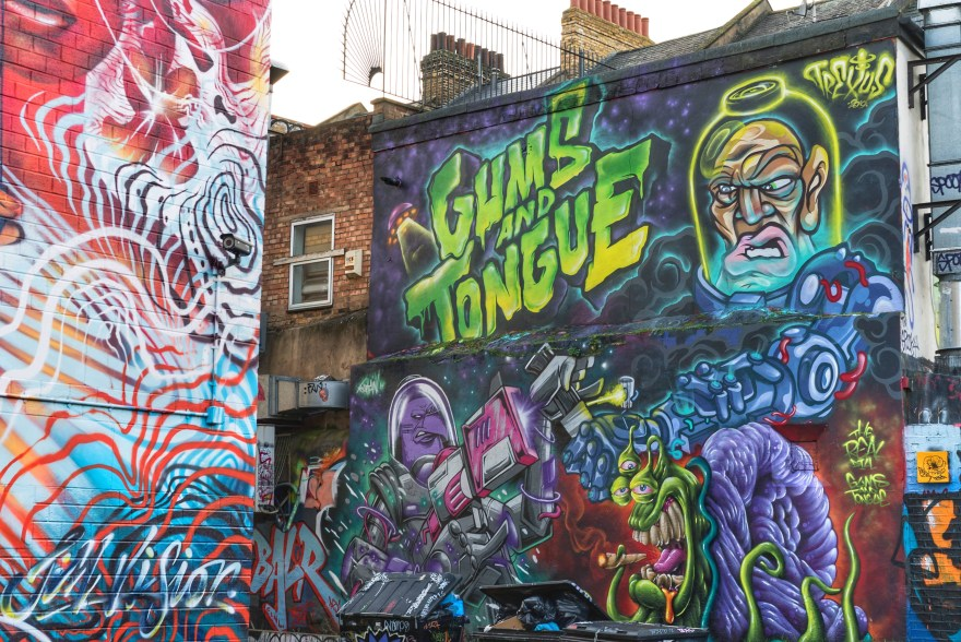 multi coloured street art in brick lane showing aliens with green text that says
