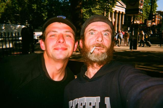 selfie of a bearded man with a joint in his mouth and another man with a hat who are both homeless in London