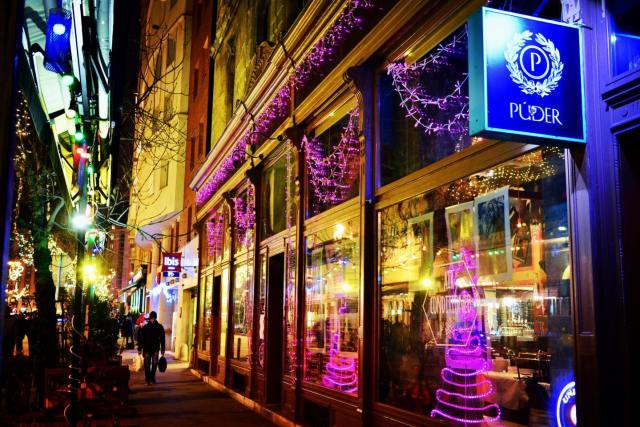 """pink and neon blue christmas lights in the front window of a bar in budapest which has a sign outdside that  says """"puder"""""""