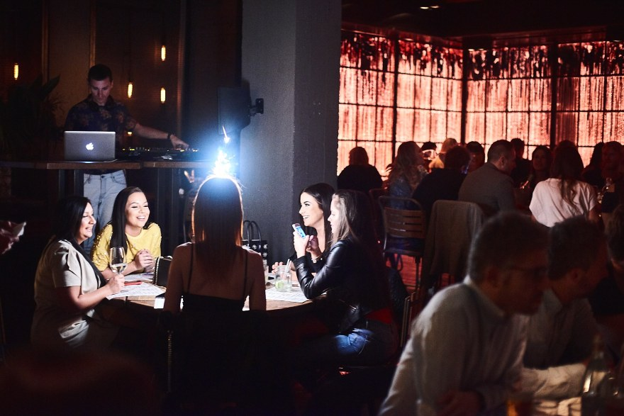 restaurant with a red backdrop packed full of people and DJ whose light is shining on a table with five girls